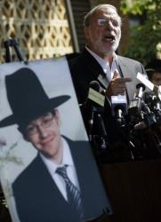 New York Assemblyman Dov Hikind addresses a gathering as he stands near a photograph of Aharon Sofer, 23, Tuesday in Lakewood, NJ.