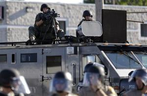 A police tactical team moves in to disperse a group of protesters in Ferguson, Mo., Wednesday, Aug. 13, 2014.