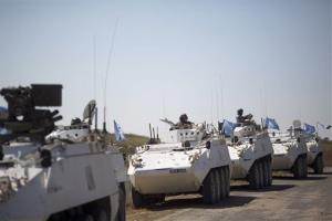 Armored vehicles of UN peacekeepers of the United Nations Disengagement Observer Force, also known as UNDOF, wait to cross from the Israeli-controlled Golan Heights to Syria on Aug. 28, 2014.