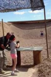 In this Aug. 25, 2014 image made from video provided by the Mohave County Sheriff Department, firing-range instructor Charles Vacca, left, shows a 9-year old girl how to use an Uzi.