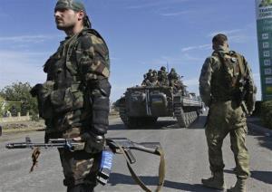 Pro-Russian rebels watch as Ukrainian troops evacuate from the rebel-held town of Starobesheve, eastern Ukraine, Saturday.