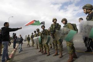 A Palestinian waves a national flag in front of Israeli soldiers during a protest against the building of settlements at Gush Etzion junction, near the West Bank town of Bethlehem.