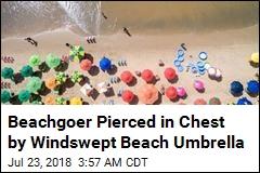 Windswept Beach Umbrella Pierces Woman's Chest